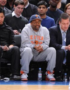 Spike Lee surrounded by his supporters in an elite seat at a NY Nicks game