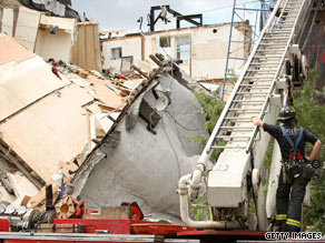 Building collapse as a fire man looks on...