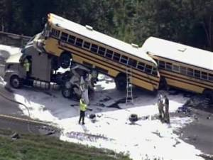 Bus collides with tractor trailer, and a car is squashed underneath the bus.