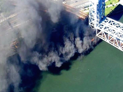 A fire eerupts under the 138th Street lift bridge, which carries all Metro-North trains.