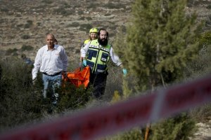 Israeli recuers carry the body of Christine Logan out of the woods where she was murdered.