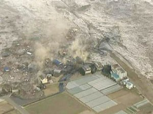 A tsunami carries  in Kamaishi city port